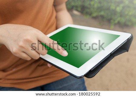 Women holding tablet  in the park - stock photo
