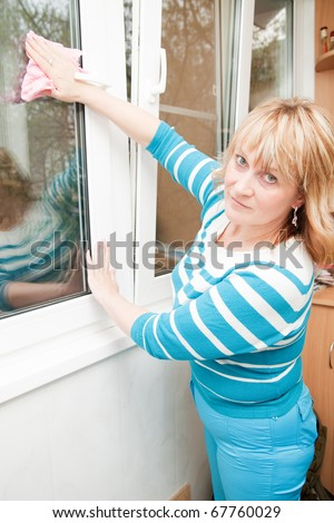 Women in blue clothing cleaning a window