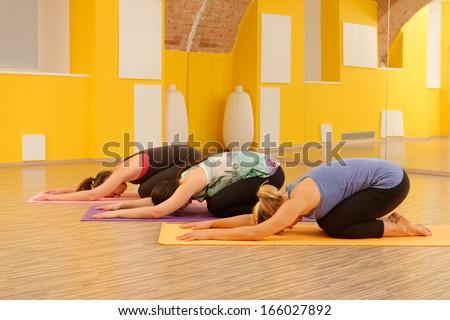 Women in child's pose in yoga class in fitness studio  - stock photo
