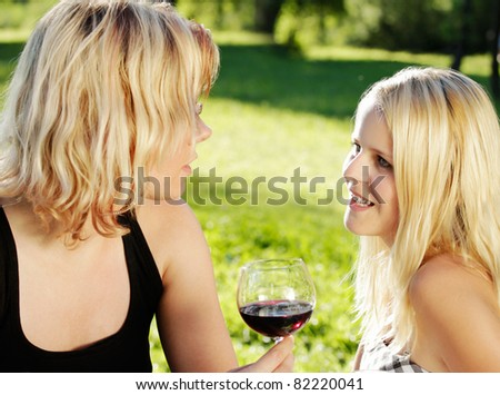 Women in conversation. Summer outdoor shot in the countryside. - stock photo