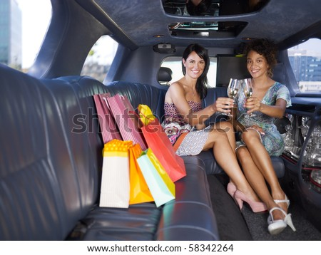 women in limousine toasting with champagne. Horizontal shape, full length, copy space