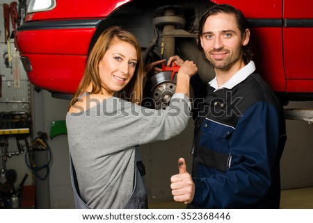 Women in male-dominated professions: Auto mechanic is happy with the success of a female trainee during maintenance of the brake disc of a car in a garage. Concept for the fact that more and more - stock photo