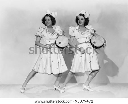 Women in matching outfits playing drums - stock photo