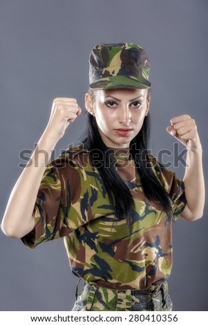 Women in military clothes boxing to the camera - stock photo