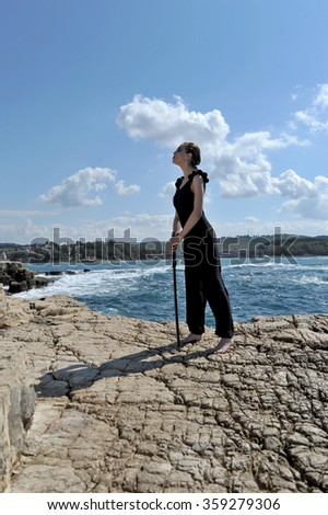 women in nature on the rocks with sword