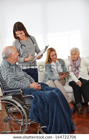 Women in nursing service doing survey under senior citizens with clipboard and tablet computer - stock photo