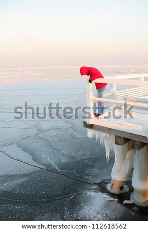Women in red. Pier, jetty  on the sea - ice - floe. Poland, Gdynia - stock photo