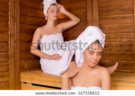 Women in sauna. Two attractive women wrapped in towel relaxing in sauna and keeping eyes closed - stock photo