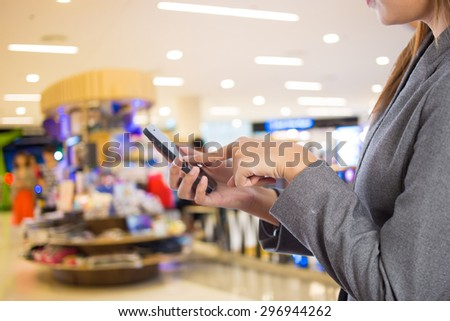 Women in shopping mall using mobile phone. - stock photo