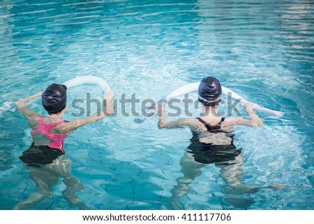 Women in the pool with foam rollers at the leisure center - stock photo