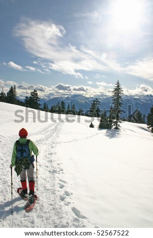 Women in the winter snow shoe hiking. - stock photo