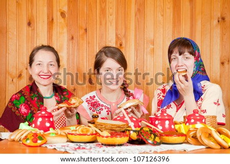 Women in traditional clothes celebrating Shrovetide and eats pancake