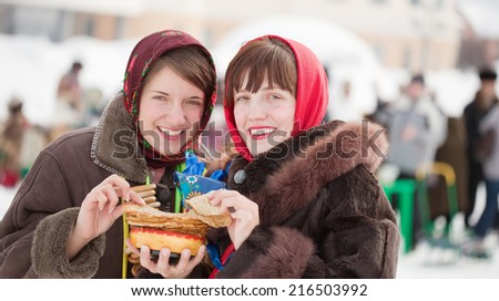 Women in traditional  clothes eating pancake during  Shrovetide - stock photo