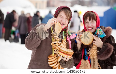 Women in traditional  clothes tasting pancake  during  Shrovetide - stock photo