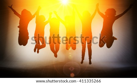Women jumping high in bright light - stock photo
