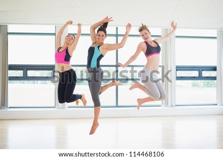 Women jumping in fitness studio at the gym