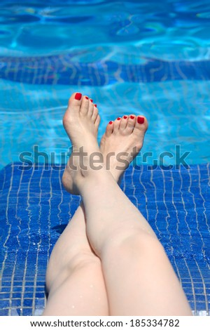 Women legs at blue water of swimming pool - stock photo