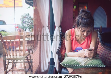 women lifestyle used a mobile phone in cafe coffee shop with texting message on app smartphone playing social network - stock photo