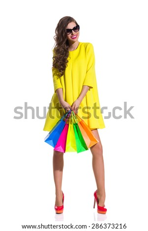 Women Likes Shopping. Smiling elegance young woman in sunglasses, red high heels and yellow mini dress standing and holding colorful shopping bags. Full length studio shot isolated on white. - stock photo