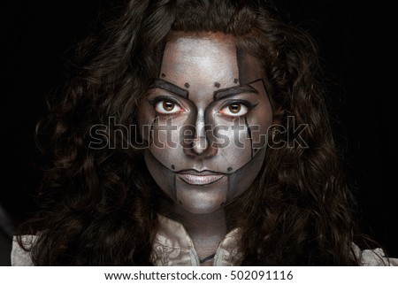 women look into camera with silver body art on face