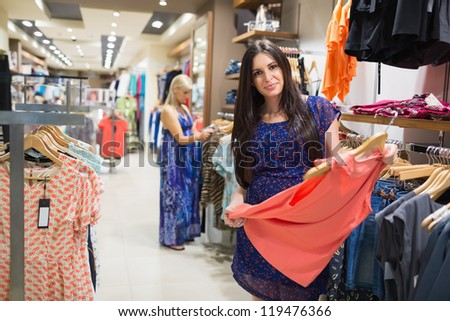 Women looking at clothes in clothes store - stock photo