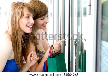 Women looking in shop window - stock photo