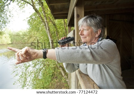 Women looking through binoculars - stock photo