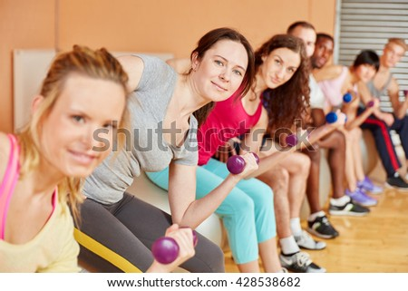 Women making exercise with weights during fitness class at the gym - stock photo