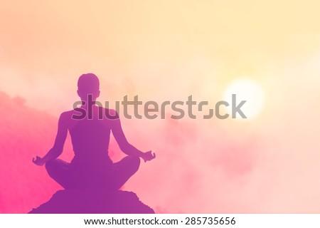 women meditating pastel on high mountain in sunset background - stock photo