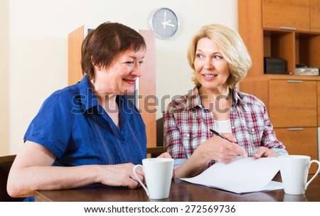 Women notary officer helping aged client drawing up of will - stock photo