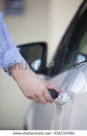 Women opening car door with key
