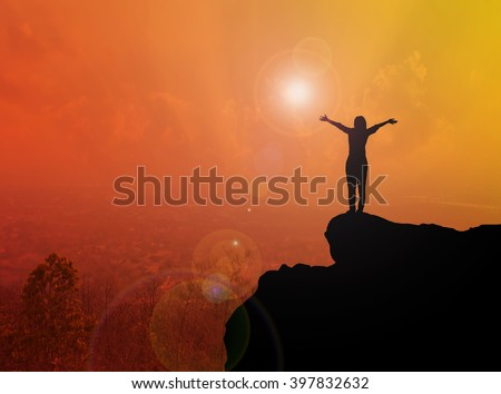 Women or girl silhouette standing on cliff in freedom gesture with blurred city top view and sunlight effect with copy space, freedom concept, welcome twilight world and happy feeling - stock photo