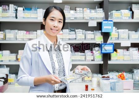 women pharmacist pharmacy pouring drugs into Tray - stock photo