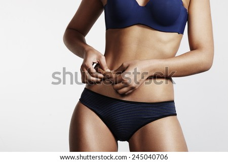 women pinch a fat on her abdomen - stock photo