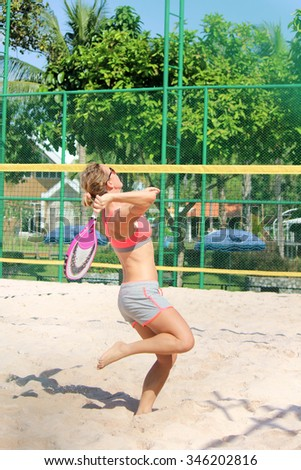 Women player plays beach tennis. - stock photo