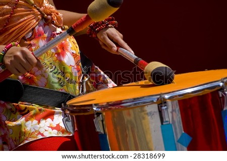 Women playing the orange drum. - stock photo