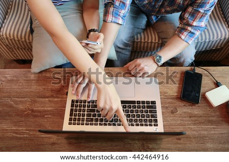women pointing laptop screen and man typing laptop on wood table, internet of things.Couple people working on laptop while discussion and shopping online together, relationship at home.