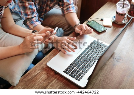 women pointing laptop screen and man typing laptop on wood table, internet of things.Couple people working on laptop while discussion and shopping online together, relationship at home. - stock photo