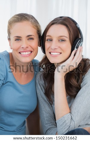 Women posing while listening to music sitting on the sofa - stock photo