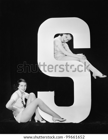 Women posing with huge letter S - stock photo