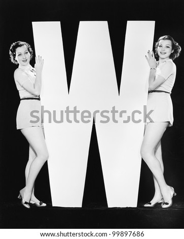 Women posing with huge letter W - stock photo