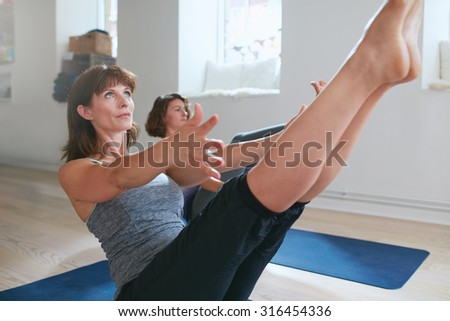 Women practicing stretching and yoga workout exercise together in a health club gym training class session. Two women practicing yoga, bending in boat pose. Performing Navasana in yoga class. - stock photo