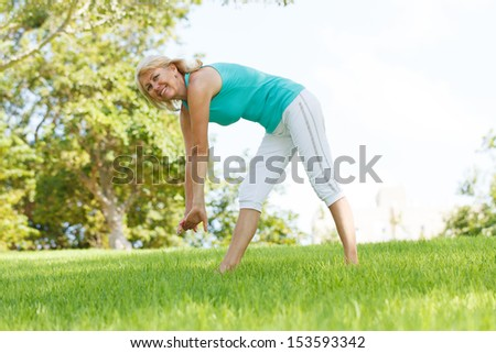 Women practising yoga in the meadow. - stock photo