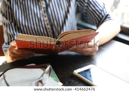 women read hardcover book on table,,hand read a book open paper page,hardworking for achievement business target concept, write idea by pen and read a book knowledge. - stock photo
