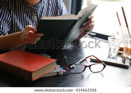 women read hardcover book on table,hand read a book open paper page,hardworking for achievement business target concept, write idea by pen and read a book knowledge. - stock photo