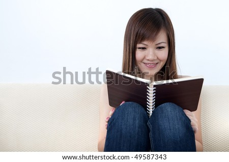 Women Reading a Book on Sofa - stock photo