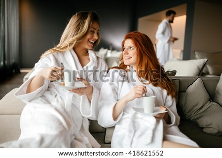 Women relaxing and drinking tea in robes during wellness weekend - stock photo