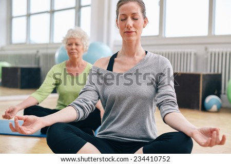 Women relaxing and meditating in their yoga class at gym. Female trainer performing a yoga routine with her class. - stock photo