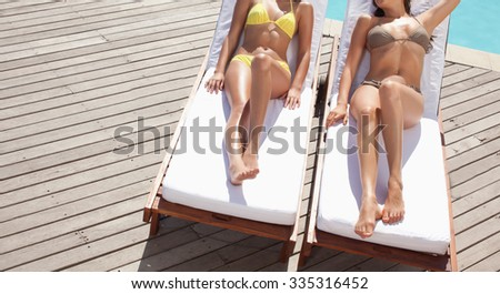 Women relaxing at the chair by the swimming pool - stock photo