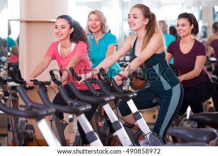 women riding stationary bicycles in modern gym for women